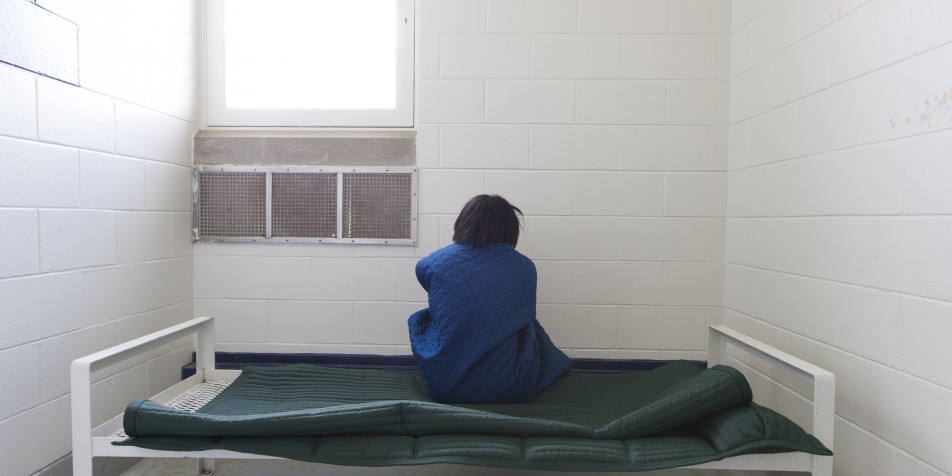 Photo of youth sitting on bed in empty solitary cell, back to camera.