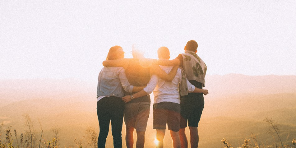 5 people hugging, facing away from camera, during sunrise.