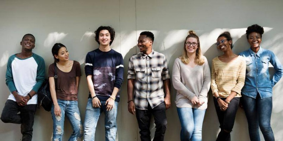 7 youth standing against a wall, smiling at the camera.