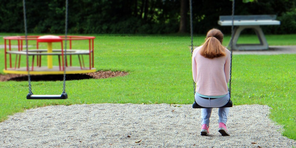 Back of teen sitting on swing, looking forlorn