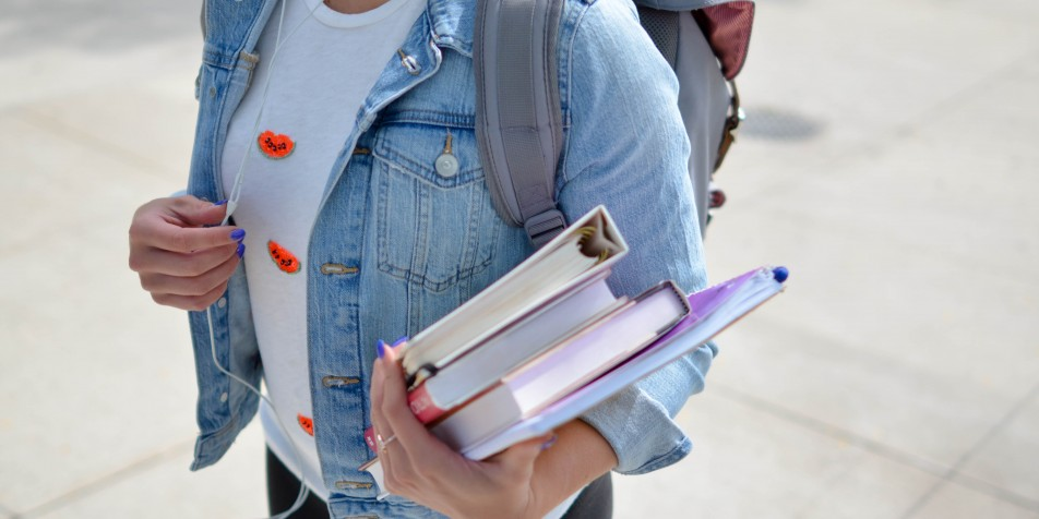Image of young woman in jean jacket, backpack and headphones, carrying textbooks.