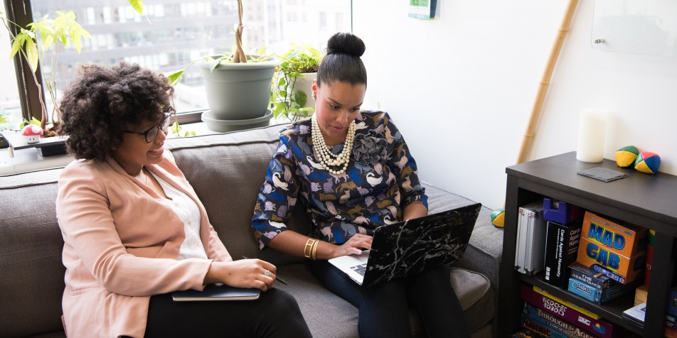 Two women seated a looking at laptop screen
