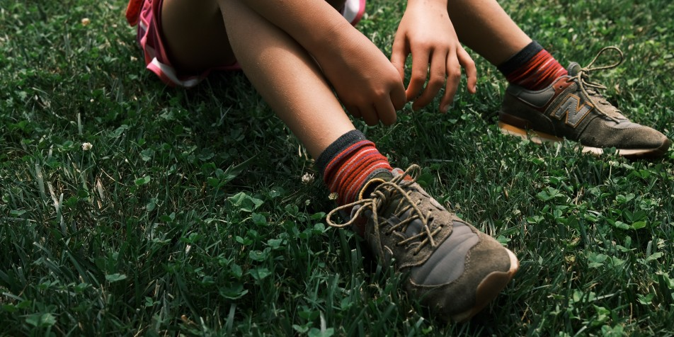 young person's knees and sneakers in grass